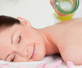 Smilling young woman having masssage oil versed on her back — Stock Photo
