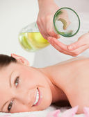 Portrait of a smilling woman getting massage oil on her back in — Stock Photo