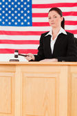 Portrait of a focused judge knocking a gavel looking at the came — Stock Photo