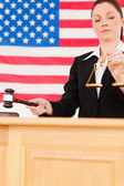 Portrait of a cute judge knocking a gavel and holding scales of — Stock Photo