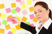 Responsible woman putting repositionable notes — Stock Photo