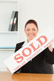 Young real estate agent holding a sold placard — Stock Photo