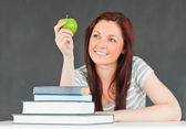 Young student in a classroom looking at an apple — Stock Photo