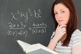Reflective young woman trying to solve an equation — Stock Photo