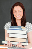 Portrait of a smiling redhead holding books — Stock Photo