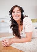 Piękna brunetka kobieta przy użyciu słuchawek leżąc na karpia — Zdjęcie stockowe