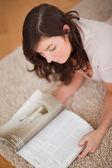 Schöne frau, die eine zeitschrift lesen, beim liegen auf einem teppich — Stockfoto