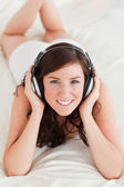 Good looking female with headphones lying — Stok fotoğraf