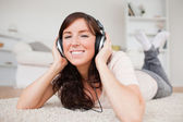 Glad brunette woman using headphones while lying on a carpet — Stock Photo