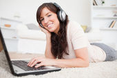 Happy brunette female relaxing with her laptop while lying on a — Stock Photo