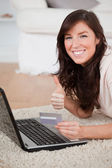 Young pretty woman making a payment with a credit card on the in — Stock Photo