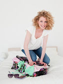 Wunderschöne blonde frau versucht ihren koffer in ihren möbeln zu schließen — Stockfoto
