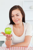 Smiling brunette showing an apple — Stock Photo