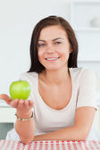 Charming brunette showing an apple — Stock Photo