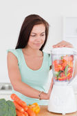 Charming brunette using a blender — Stock Photo