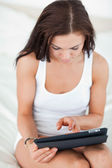 Portrait of a cute brunette using a tablet — 图库照片