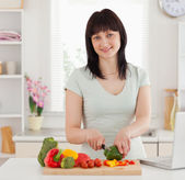 Pretty brunette woman cooking while relaxing with her laptop — Stock Photo