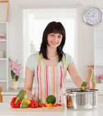 Beautiful brunette woman posing while cooking vegetables — Stockfoto
