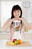 Pretty brunette woman posing with a mixer while standing — Stock Photo