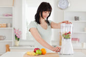 Cute brunette woman using a mixer while standing — Stock Photo