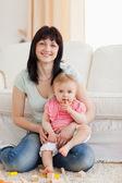 Bella donna tiene il suo bambino in braccio mentre era seduto una — Foto Stock
