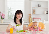 Charming brunette woman eating a salad next to her baby while si — Stock Photo