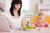 Gorgeous brunette woman eating a salad next to her baby while re — Stock Photo