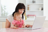 Attractive brunette woman showing her laptop to her baby while s — Stock Photo