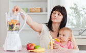 Cute brunette woman pealing a banana while holding her baby on h — Stock Photo