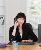 Good looking brunette woman on the phone while working on a comp — Stock Photo