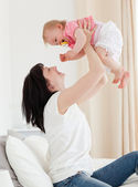 Attractive brunette woman playing with her baby while sitting on — Stock Photo