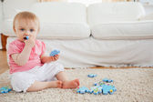 Cute baby playing with puzzle pieces while sitting on a carpet — Stock Photo