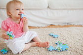 Blond baby playing with puzzle pieces while sitting on a carpet — Stock Photo
