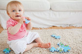 Cute blond baby playing with puzzle pieces while sitting on a ca — Stock Photo