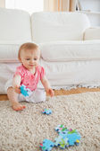 Lovely blond baby playing with puzzle pieces while sitting on a — Stock Photo