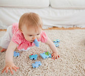 Lovely blond baby playing with puzzle pieces on a carpet — Stock Photo