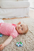 Lovely blond baby playing with puzzle pieces while lying on a ca — Stock Photo