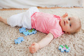 Cute blond baby playing with puzzle pieces while lying on a carp — Stock Photo