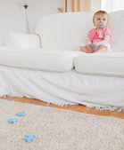 Cute blond baby playing with puzzle pieces while sitting on a so — Stock Photo