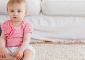 Lovely blond baby looking at the camera while sitting on a carpe — Stock Photo