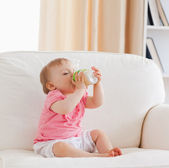 Lovely blond baby bottle-feeding while sitting on a sofa — Stock Photo