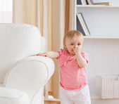Baby standing near a sofa — Stock Photo