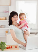 Cute woman holding her baby in her arms — Stock Photo