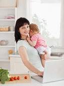Good looking brunette woman holding her baby in her arms — Stock Photo