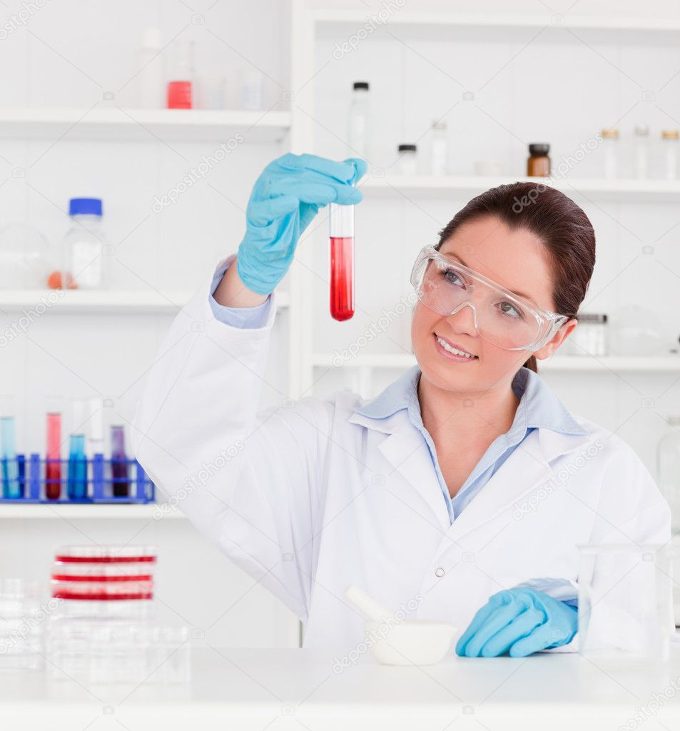 Cute scientist looking at a test tube — Stock Photo #10600864