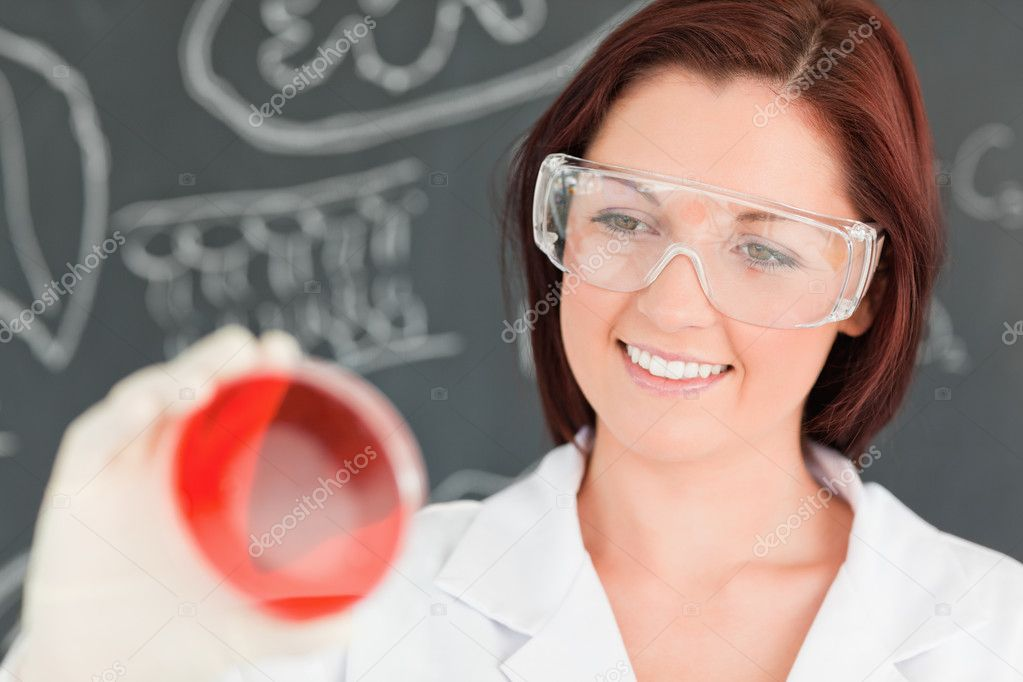 Close up of a red-haired scientist looking at a petri dish in a classroom — Stock Photo #10601337