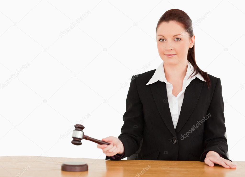 Young judge knocking a gavel smiling at the camera  against a white background — Stock Photo #10601362