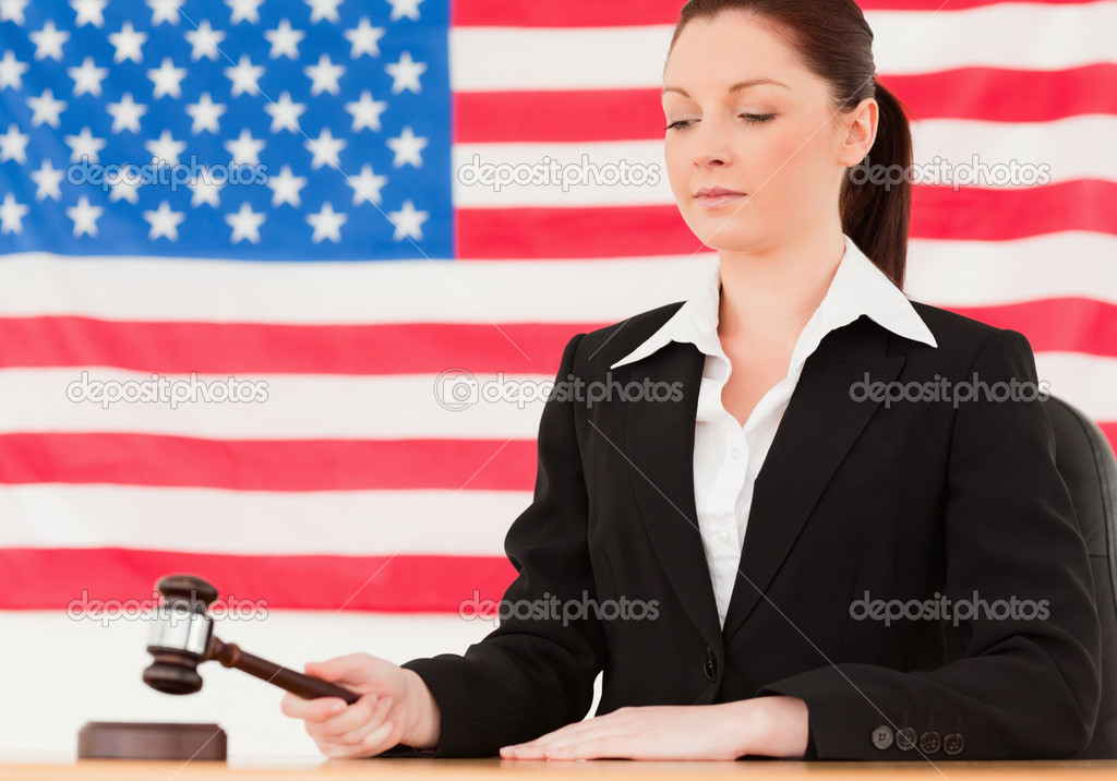 Serious young judge knocking a gavel with an American flag in the background  Stock Photo #10601366