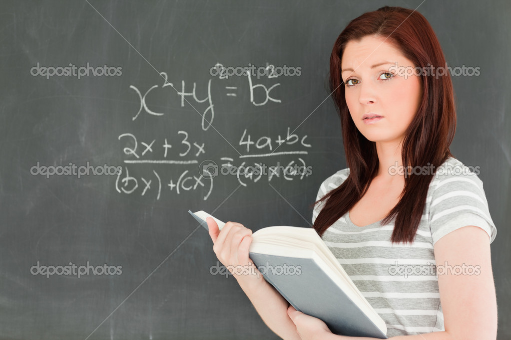 Cute woman trying to solve a mathematical equation on a blackboard in a classroom — 图库照片 #10601804