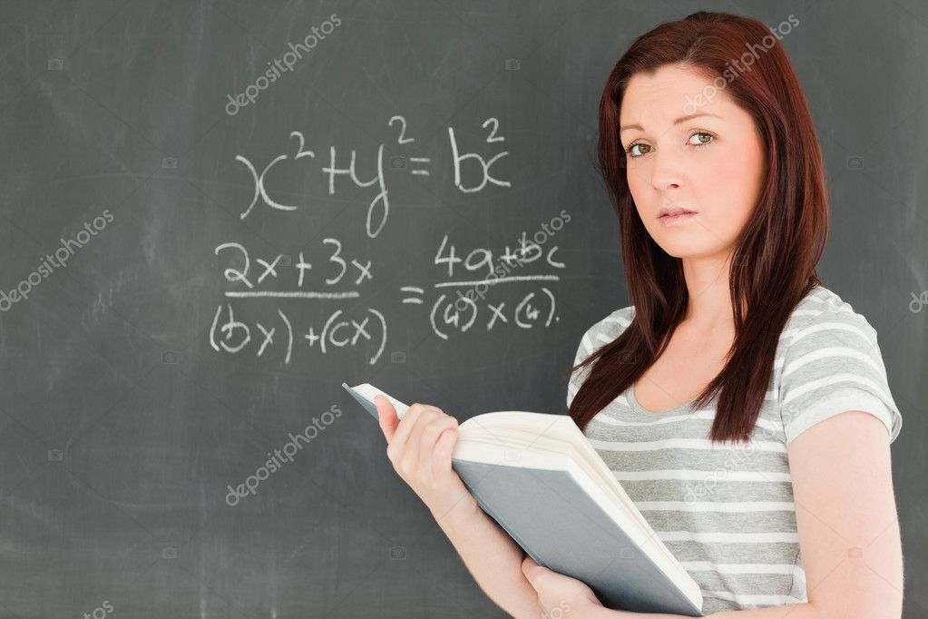 Cute woman trying to solve a mathematical equation on a blackboard in a classroom — Lizenzfreies Foto #10601804